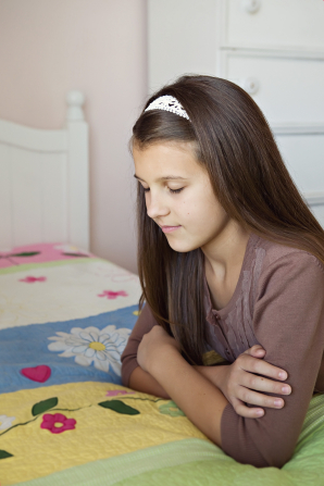 A young girl folds her arms and leans on her bed while she closes her eyes and prays.
