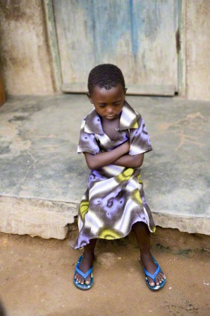 A little girl in Ghana sits on a step and folds her arms and prays.
