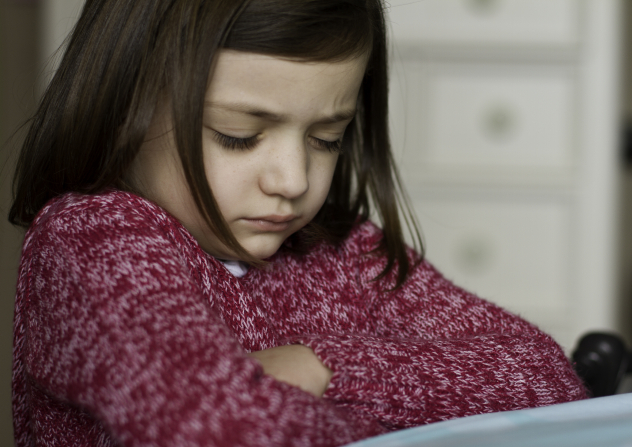 A little girl in a pink sweater folds her arms, bows her head, and closes her eyes while praying.