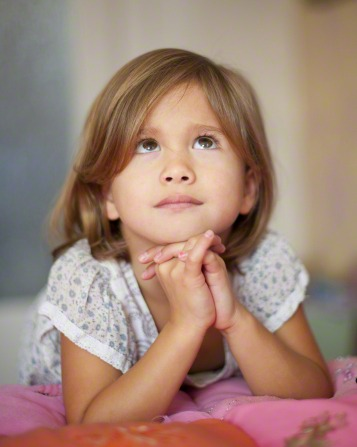 A girl kneels next to her bed, rests her elbows on her mattress, folds her hands under her chin, and looks up while praying.
