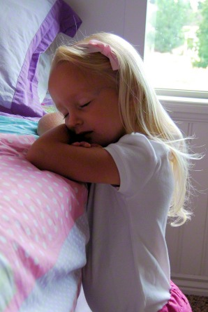 A girl wearing a white T-shirt and a pink bow in her blond hair kneels next to her bed with her eyes closed to say a prayer in the morning.