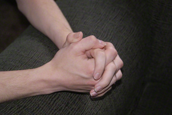 Two hands clasped together in prayer, resting on a couch cushion.