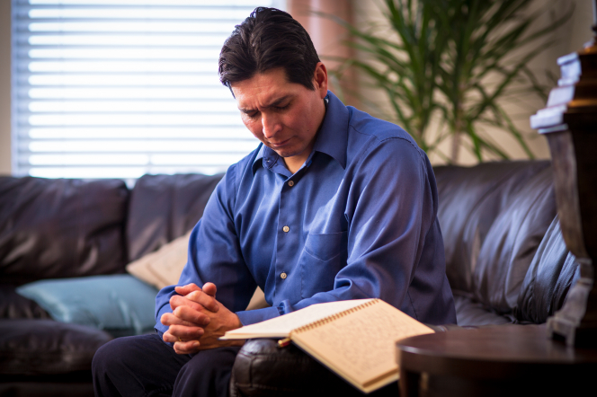 A man clasps his hands and rests them on his knee while he sits in prayer with his journal open.