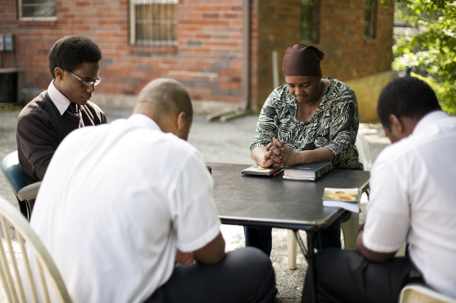 Two missionaries sit at a table outside with a man and woman and pray with them while reading the scriptures together.