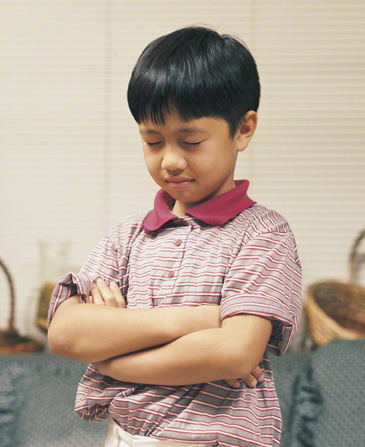 A young boy folds his arms, bows his head, and prays.