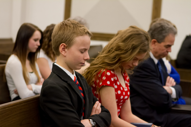 A family bow their heads and fold their arms while sitting in a pew at church and listening to a prayer.