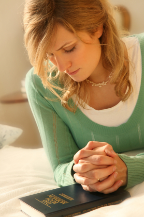 A woman prays while kneeling down and clasping her hands over a Book of Mormon.