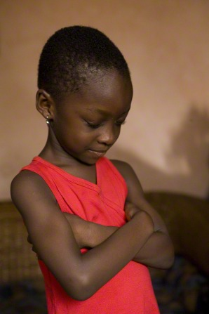 A young girl folds her arms, bows her head, and prays in her home in Ghana.