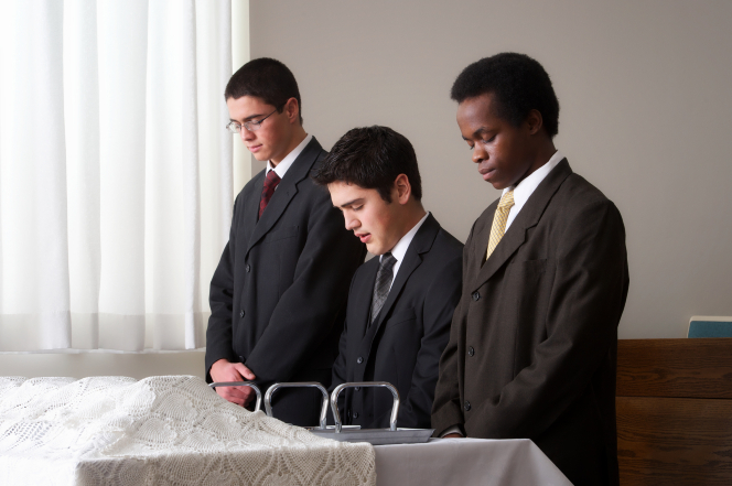 Three young men close their eyes and pray to bless the sacrament in front of them.