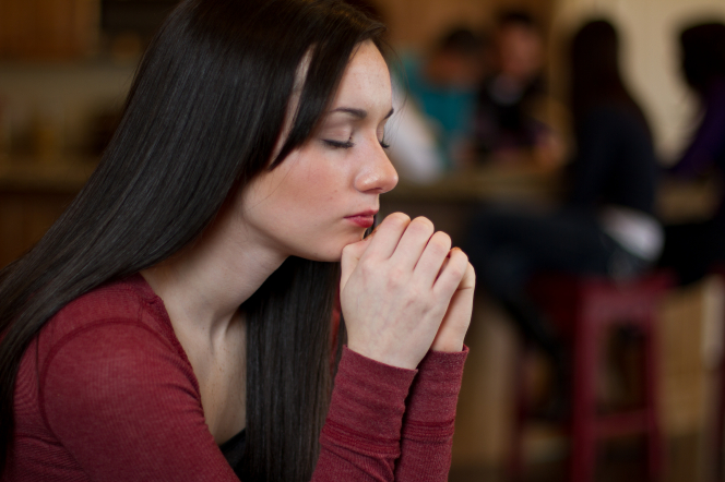 A woman clasps her hands, closes her eyes, and prays.