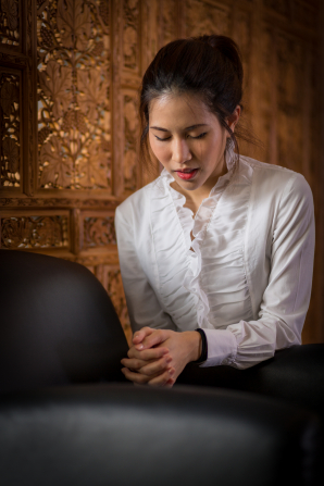A young woman in Thailand kneels by a chair, bows her head, and prays.
