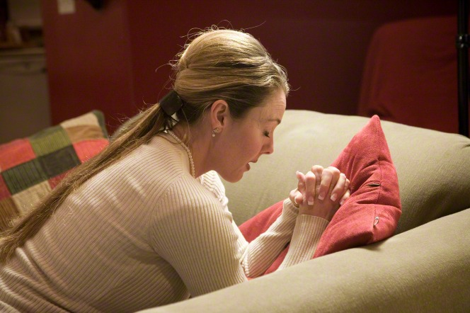 A woman kneels by the couch, clasps her hands, and rests her arms on the couch while she bows her head and prays.