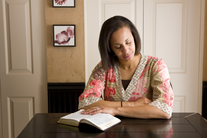 A woman closes her eyes and prays while sitting at a table with her scriptures open.