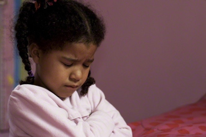 A young girl in pajamas bows her head and folds her arms to pray next to her bed.