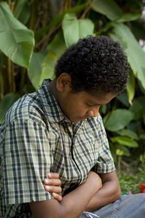 A young man with curly black hair and a green plaid shirt sits in an outdoor tropical setting and prays with head bowed and arms folded.
