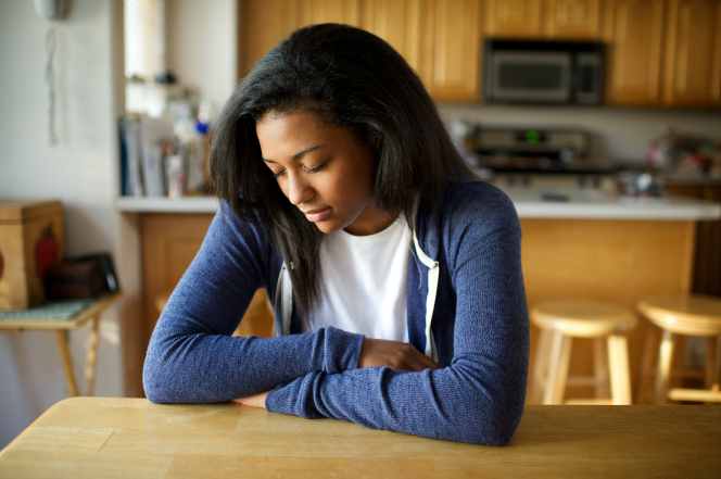 A young woman folds her arms and rests them on a table while she prays.