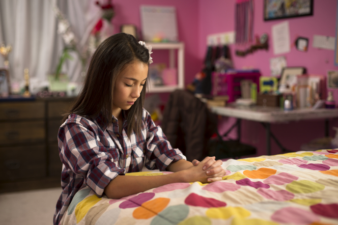 A young woman clasps her hands and rests them on her bed while she kneels and prays.
