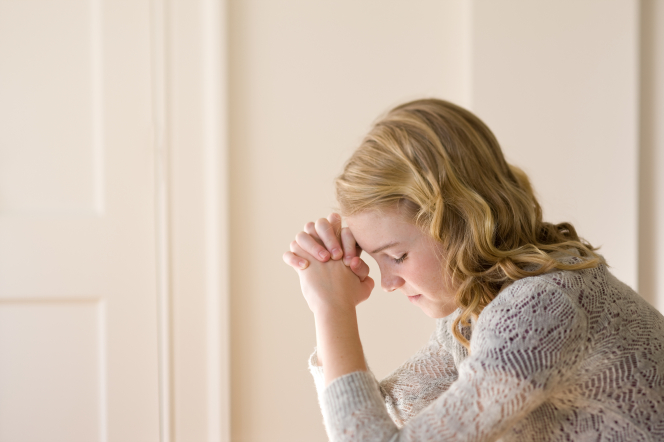 A young woman clasps her hands and rests her forehead on them, closes her eyes, and prays.