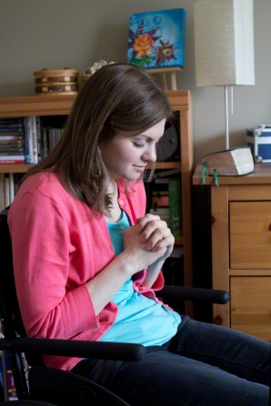 A young woman in a wheelchair closes her eyes and clasps her hands while praying.