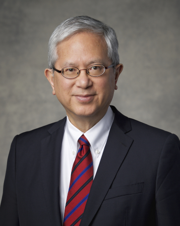 The official portrait of Elder Gerrit W. Gong of the Presidency of the Seventy of The Church of Jesus Christ of Latter-day Saints, in a dark suit and a red and blue striped tie against a gray background.
