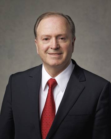 The official portrait of Elder Lynn G. Robbins of the Presidency of the Seventy of The Church of Jesus Christ of Latter-day Saints, in a dark suit and a red tie against a gray background.