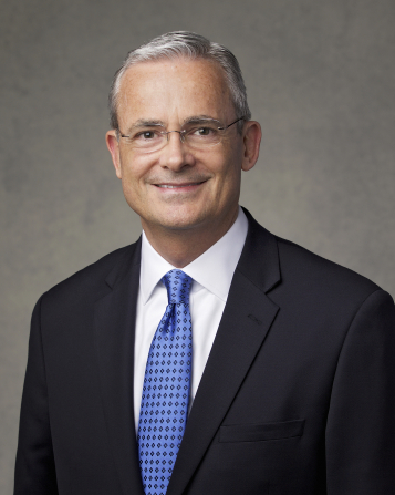 The official portrait of Elder Patrick Kearon of the Presidency of the Seventy of The Church of Jesus Christ of Latter-day Saints, in a dark suit and a blue tie against a gray background.
