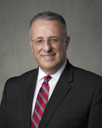 The official portrait of Elder Ulisses Soares of the Presidency of the Seventy of The Church of Jesus Christ of Latter-day Saints, in a dark suit and a red and blue striped tie against a gray background.