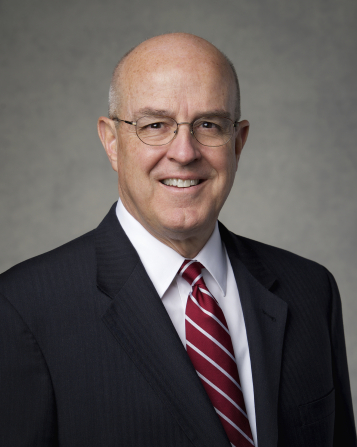 The official portrait of Elder L. Whitney Clayton, Senior President of the Presidency of the Seventy of The Church of Jesus Christ of Latter-day Saints, in a dark suit and a red striped tie against a gray background.