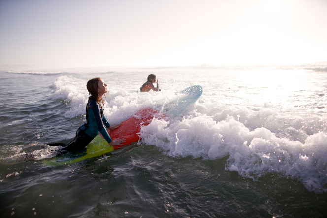 Two women in wet suits paddle into an ocean wave on their surfboards.
