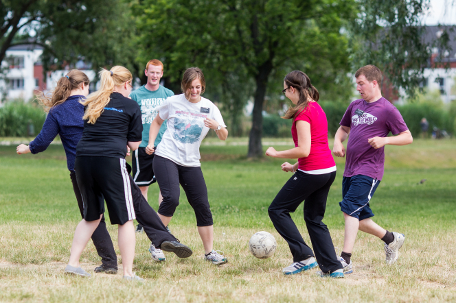 A group of elder and sister missionaries playing soccer in the park together.