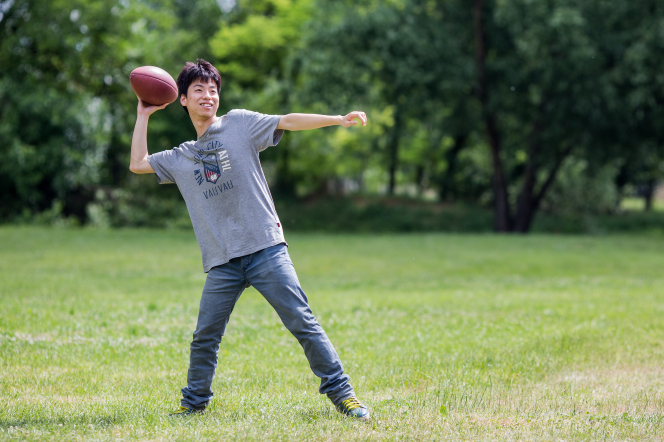 A young man prepares to throw a football while outside at a park.