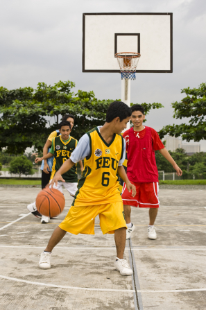 Four teenage boys in jerseys playing basketball on a court outside.