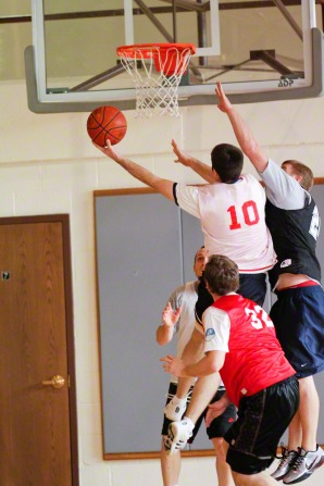 A man aims to shoot a basketball in a hoop with three other men around him.