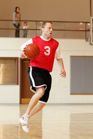 A man in a red jersey, black shorts, and tennis shoes plays basketball at a church gym, with his wife and child watching from above.
