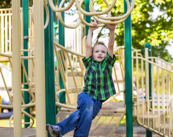 A young boy in a green and blue plaid shirt swings on monkey bars at a park.