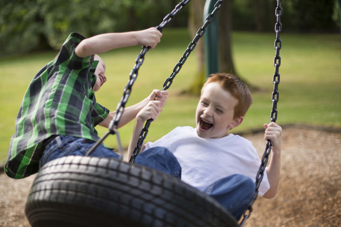 Two boys outside sit in a tire swing and hold onto the chains.