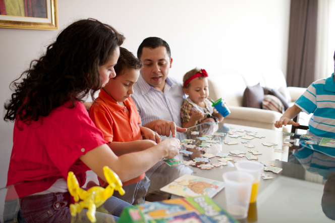 A mother, father, and their three children sit at a table and build a puzzle together.