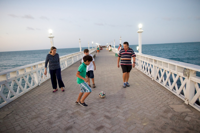 A father, mother, and their two sons play soccer on a pier, with the ocean on both sides.