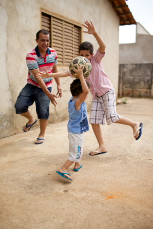 A father and his two sons running and jumping outside by a building, with the youngest son holding a ball above his head.