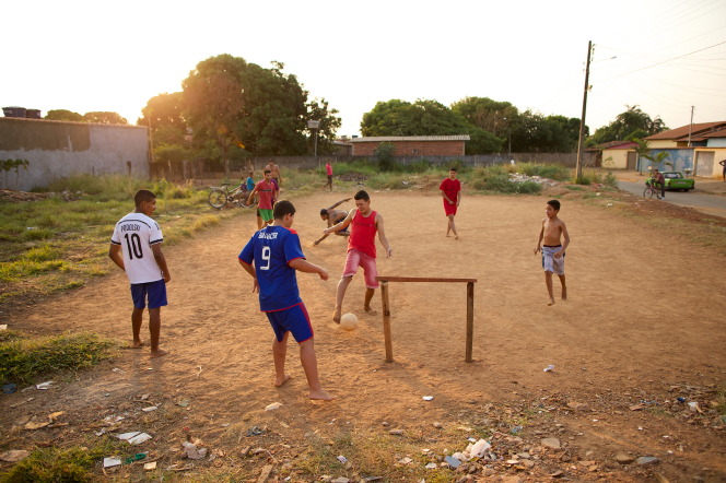 Young men from Brazil playing soccer barefoot on a dirt field, with the sun setting over the distant trees.