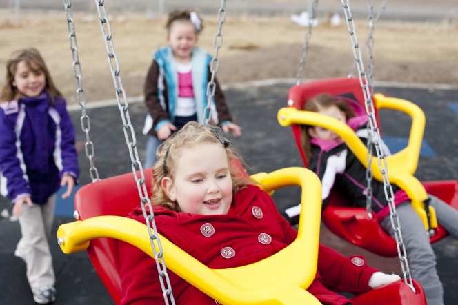 Two girls in coats push two other girls on red and yellow swings.