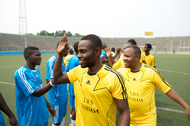 Men in yellow jerseys line up on a grass field at a soccer game, giving high fives to the opposite team of men in blue jerseys.