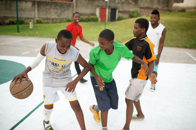 A young man plays with a group of other young men on an outdoor court in Africa, dribbling a basketball and guarding himself from another player.