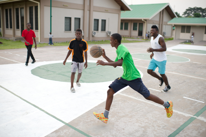 A young man in a green shirt, gray shorts, and yellow shoes quickly runs and dribbles a basketball on an outdoor court while other young men approach him.