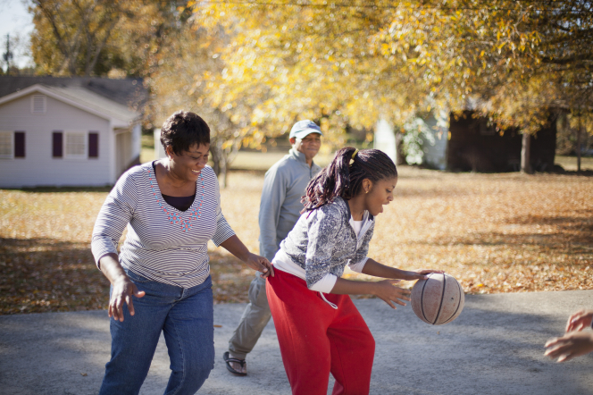A mother and father play basketball with their teenage children in the driveway.