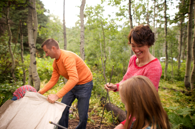 A mother and father set up a tent with their two children outside in the trees.