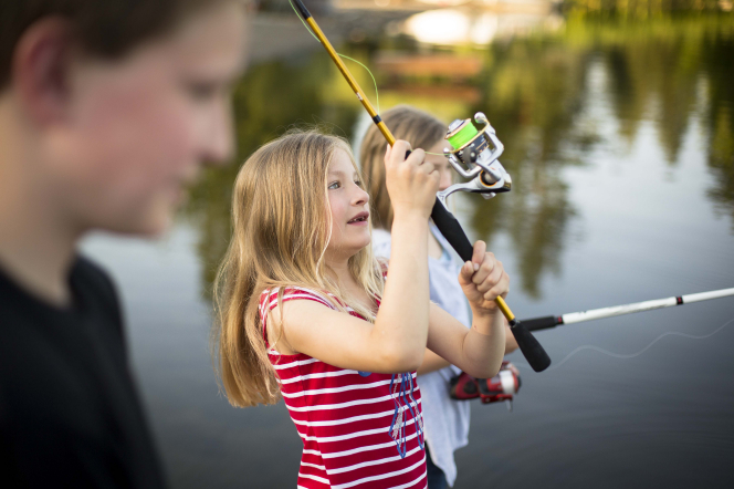 A young girl with light brown hair and a red and white striped shirt holding a fishing pole up in the air by a lake.