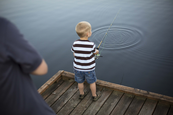 A little boy stands on a pier next to his father and holds a fishing pole with a line in the water.