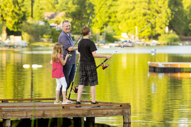 A father fishes with his two children. All three stand on a pier and hold fishing poles.
