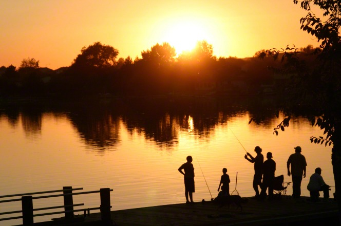 A silhouette image of a family fishing together at sunset.